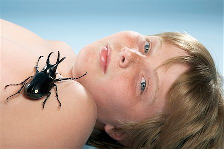 shirtless black boy - Shirtless boy (10-11) lying down with large beetle crawling on chest, portrait, close-up Stock Photo - Premium Royalty-Free, Code: 6106-07022255