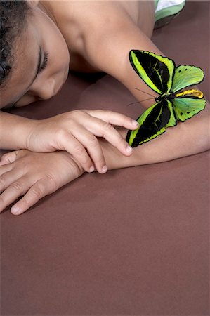 shirtless black boy - Boy (4-5) lying down and looking at large green butterfly on arm Stock Photo - Premium Royalty-Free, Code: 6106-07022227