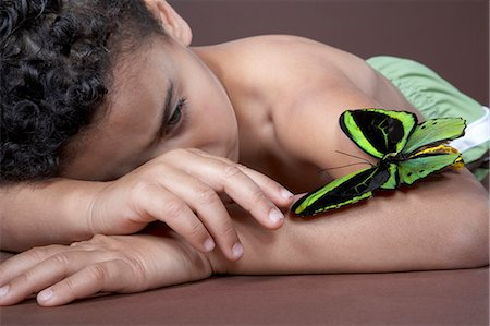 shirtless black boy - Boy (4-5) lying down and looking at large green butterfly on arm, close-up Stock Photo - Premium Royalty-Free, Code: 6106-07022230