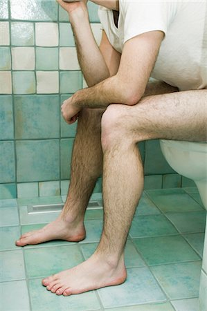 Man sitting on toilet Stock Photo - Premium Royalty-Free, Code: 6106-07022474