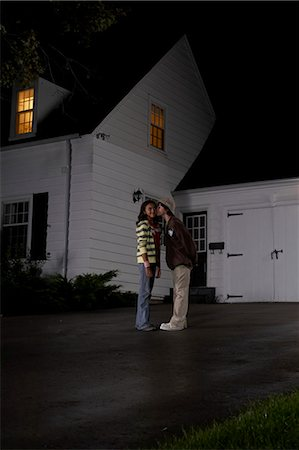 Boy (12-13) kissing girl (12-13), girl turning head, in driveway in front of house, side view, night Stock Photo - Premium Royalty-Free, Code: 6106-07022553