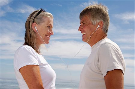 descriptive - Mature couple sharing earphones, standing face to face against sea, profile Stock Photo - Premium Royalty-Free, Code: 6106-07022571