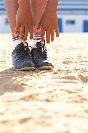 Boy (12-13) doing gymnastics on sand, low section Stock Photo - Premium Royalty-Free, Code: 6106-07022897