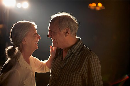 descriptive - Senior couple outdoors at night, looking in eyes and smiling, profile Stock Photo - Premium Royalty-Free, Code: 6106-07023386