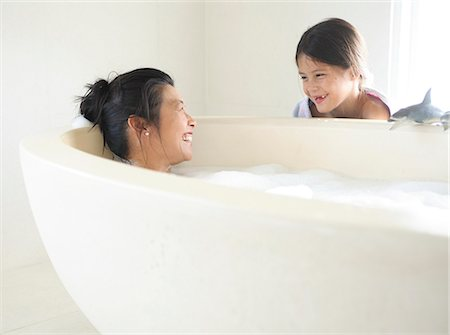 Mother and daughter (8-9) in bathroom, woman taking bath Stock Photo - Premium Royalty-Free, Code: 6106-07023748