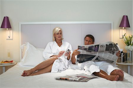 Couple in bathrobes relaxing on bed, man reading newspaper Stock Photo - Premium Royalty-Free, Code: 6106-07024060
