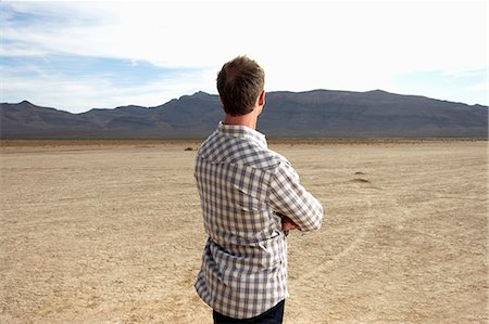 descriptive - USA, Nevada, mature man in desert looking at mountain range, rear view Stock Photo - Premium Royalty-Free, Code: 6106-07024186