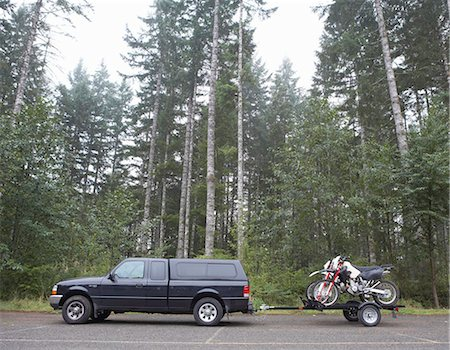Truck towing motorbikes on trailer in forest, side view Stock Photo - Premium Royalty-Free, Code: 6106-07024371