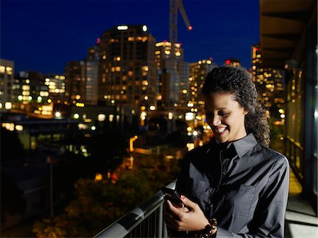 descriptive - Businesswoman using mobile phone on balcony at night Stock Photo - Premium Royalty-Free, Code: 6106-07024758