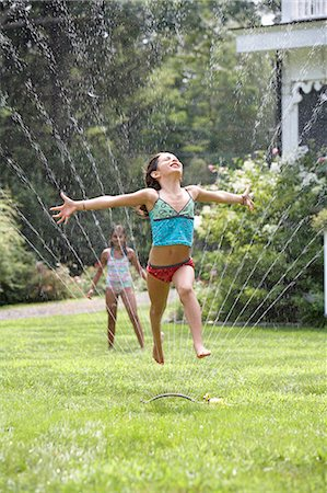 Two girls (8-9) playing in garden, one jumping through sprinkler Stock Photo - Premium Royalty-Free, Code: 6106-07024774