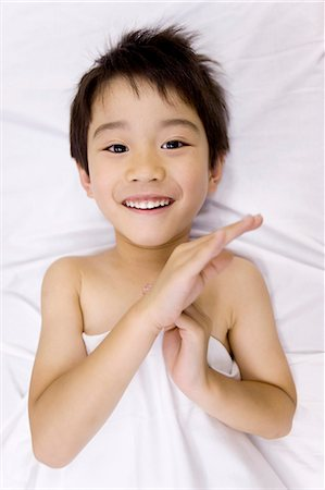 descriptive - Boy (5-6) lying on bed, smiling, portrait Stock Photo - Premium Royalty-Free, Code: 6106-07025079