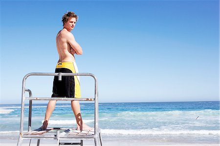 Young man standing on lifeguard podium, rear view Stock Photo - Premium Royalty-Free, Code: 6106-07025190