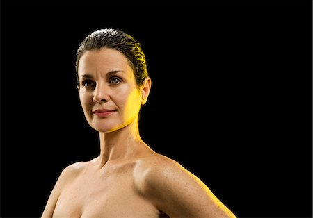 Naked mature woman against black background Stock Photo - Premium Royalty-Free, Code: 6106-07025285