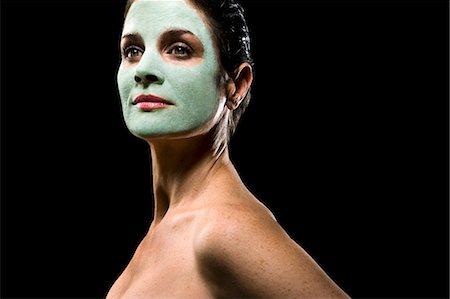 Naked mature woman wearing facial mask, posing against black background Stock Photo - Premium Royalty-Free, Code: 6106-07025286