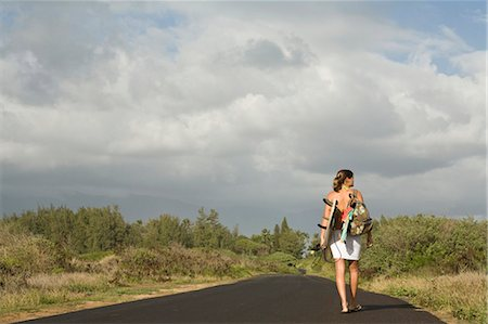 road landscape - Young woman carrying surfboard on country road Stock Photo - Premium Royalty-Free, Code: 6106-07026098