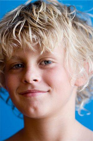Portrait of blonde boy (12-13), studio shot Stock Photo - Premium Royalty-Free, Code: 6106-07026344
