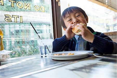 Boy eating Hamburger in restaurant Stock Photo - Premium Royalty-Free, Code: 6106-07030049