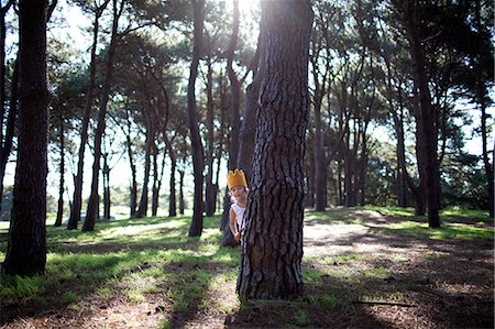 Little boy in crown playing hide seek in forest Stock Photo - Premium Royalty-Free, Code: 6106-07120949