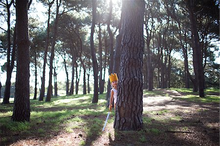 LIttle boy with crown and sword hiding in forest Stock Photo - Premium Royalty-Free, Code: 6106-07120952