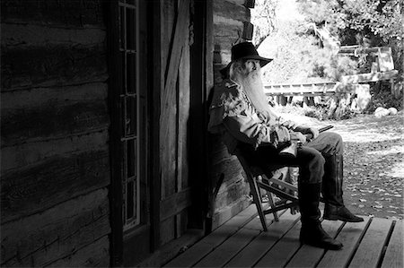 Old cowboy with a gun on a chair Stock Photo - Premium Royalty-Free, Code: 6106-07120994