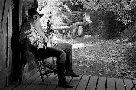 Old cowboy with gun on a chair Stock Photo - Premium Royalty-Free, Code: 6106-07121000