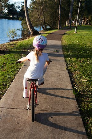 Young Girl Learning to Ride Bicycle Stock Photo - Premium Royalty-Free, Code: 6106-07349038