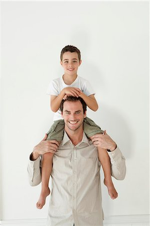 Happy Father Carrying His Son On Shoulder Stock Photo - Premium Royalty-Free, Code: 6106-07349441