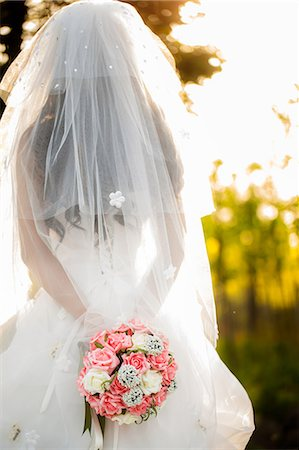 bride in veil holding flowers outdoor Stock Photo - Premium Royalty-Free, Code: 6106-07349525