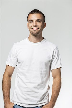 Young man with blue jeans and T-Shirt smiling Stock Photo - Premium Royalty-Free, Code: 6106-07350720
