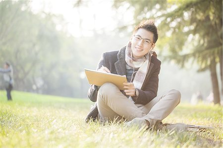 Young student on campus lawn Stock Photo - Premium Royalty-Free, Code: 6106-07350975