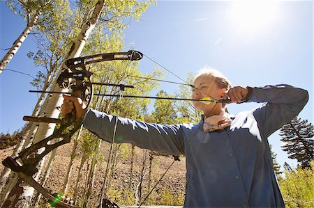 Woman shooting compound bow at target in woods. Stock Photo - Premium Royalty-Free, Code: 6106-07454777