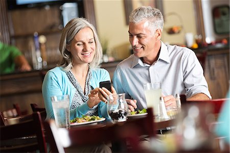 Woman showing her date something on cell phone Stock Photo - Premium Royalty-Free, Code: 6106-07454833