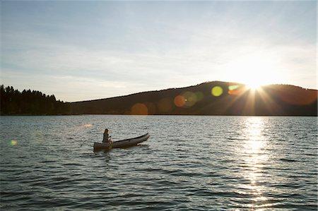 Woman paddling canoe at sunset on lake. Stock Photo - Premium Royalty-Free, Code: 6106-07454955
