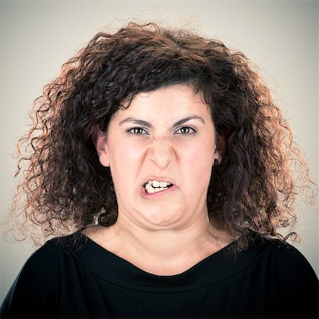Young long curly hair lady grimacing portrait Stock Photo - Premium Royalty-Free, Code: 6106-07455206
