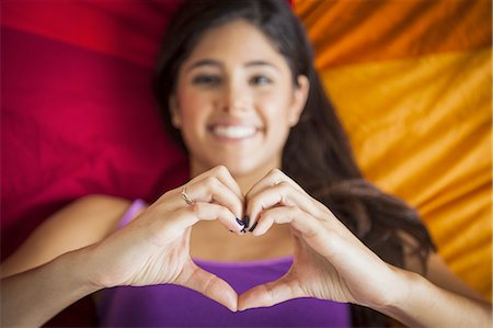 Teenage girl on bed making heart shape with hands Stock Photo - Premium Royalty-Free, Code: 6106-07492985