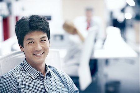 portrait - Asian man sitting in an office smiling Stock Photo - Premium Royalty-Free, Code: 6106-07493396