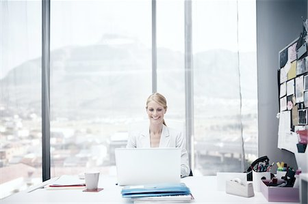 Smiling businesswoman in her office Foto de stock - Sin royalties Premium, Código: 6106-07493402