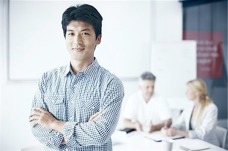 east asian - Portrait of a businessman with colleagues in back Stock Photo - Premium Royalty-Free, Code: 6106-07493411