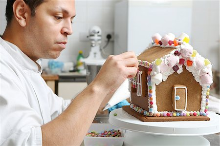 Artisan baker decorating gingerbread house Stock Photo - Premium Royalty-Free, Code: 6106-07594404
