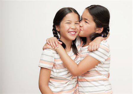 preteen kissing - Young sisters in braids, laughing Stock Photo - Premium Royalty-Free, Code: 6106-07594818