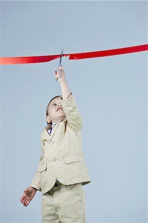 Boy (3-5) cutting ribbon Stock Photo - Premium Royalty-Free, Code: 6106-07539146