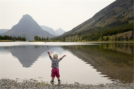 Toddler stands in mountain lake with arms raised Stock Photo - Premium Royalty-Free, Code: 6106-07539219
