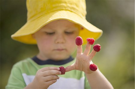 Male toddler with raspberries on his fingers Stock Photo - Premium Royalty-Free, Code: 6106-07539461