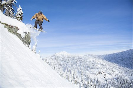 Snowboarder hucks cliff on sunny day Stock Photo - Premium Royalty-Free, Code: 6106-07539517