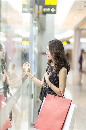shopping mall - young woman looking through a shop window Stock Photo - Premium Royalty-Free, Code: 6106-07539531