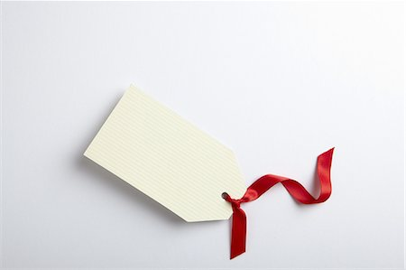 Blank gift tag with red ribbon Stock Photo - Premium Royalty-Free, Code: 6106-07602272