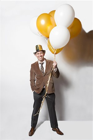 man smiling on white holding balloons on new years Stock Photo - Premium Royalty-Free, Code: 6106-07602434
