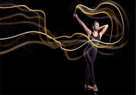 Gymnast waving golden sparkly ribbon Stock Photo - Premium Royalty-Free, Code: 6106-07761903