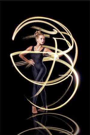 Dancer making beautiful yellow light rays Stock Photo - Premium Royalty-Free, Code: 6106-07761904