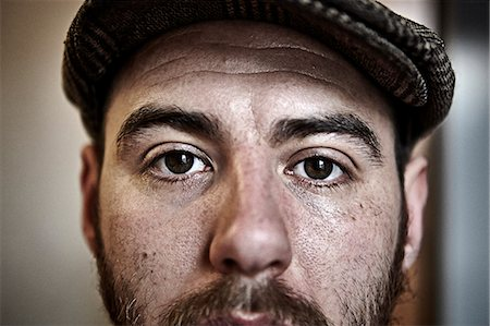 Extreme close up of male in flat cap with beard Stock Photo - Premium Royalty-Free, Code: 6106-08172601